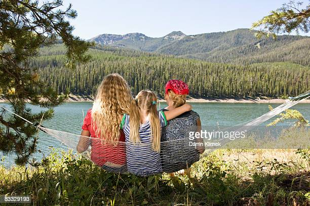 Sister sitting on hammock together by lake