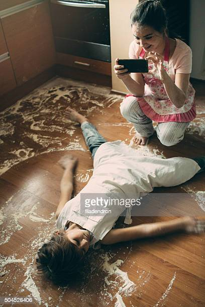 Sister taking photo of her brother lying on floor
