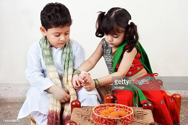 Sister tying a rakhi to her brother