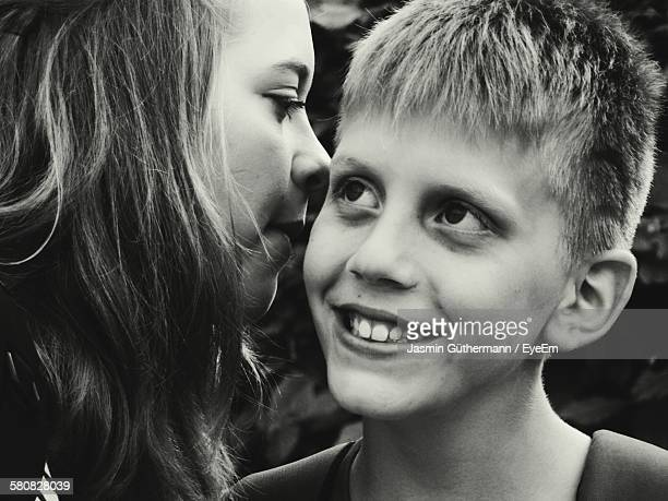 Sister Whispering To Younger Brother