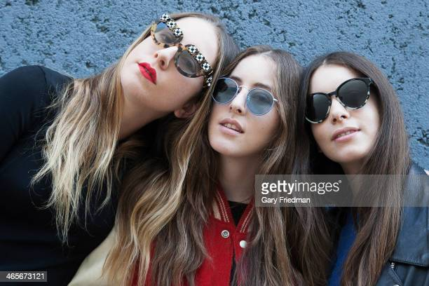 Sisters and members of the band Haim Alana Haim Este Haim Danielle Haim are photographed for Los Angeles Times on October 17 2013 in Hollywood...