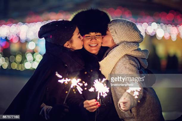 Sisters are kissing their mother and playing with fireworks at Christmas