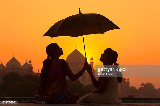 Sisters at sunset with Taj Mahal beyond