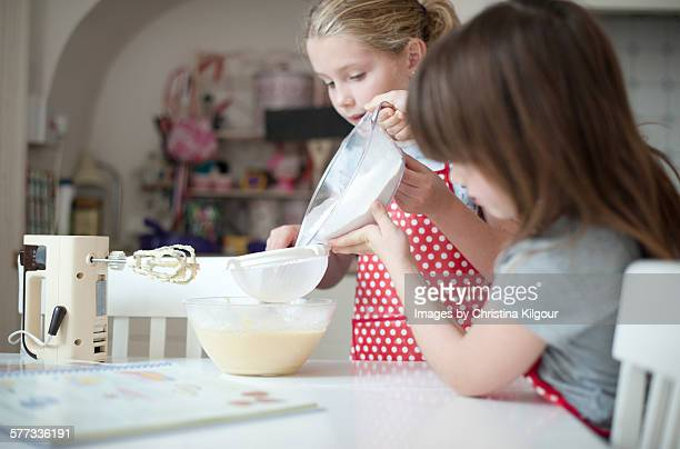 Sisters baking a cake together