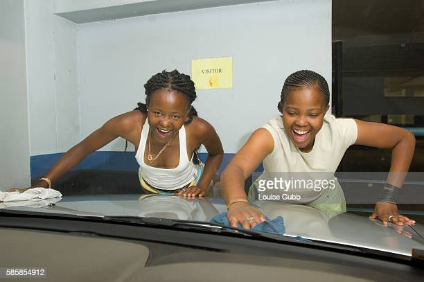 Sisters Bongile Nkosi and Victoria polish a car as part of an allgirl carwash syndicate during the annual Market Day at CIDA Victoria is at CIDA...