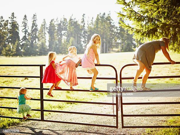 Sisters climbing over gate to field