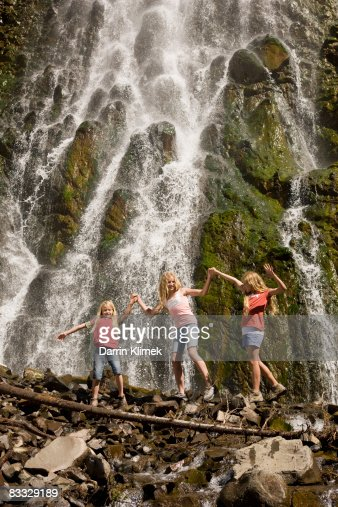 Sisters crossing waterfall together
