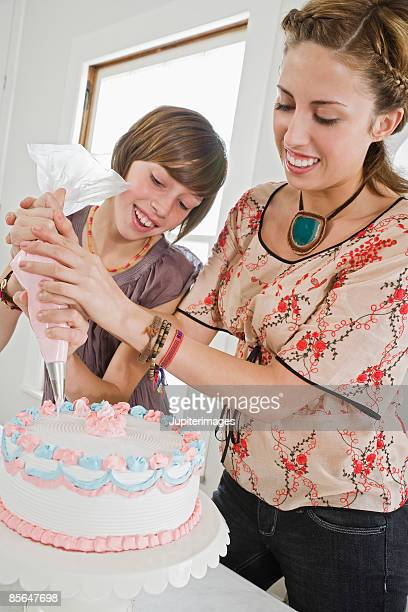 Sisters decorating cake