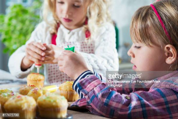Sisters decorating cakes in kitchen
