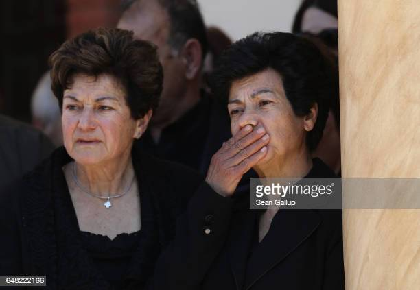 Sisters Dina Mita and Androula Savva look on as soldiers arrive with a coffin that contains the remains of their brother Georgiou Theodoulos...