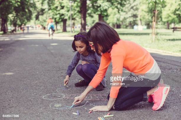 Sisters drawing with chalk in the park