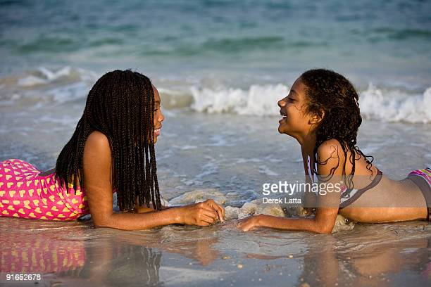 Sisters facing each other on the beach.