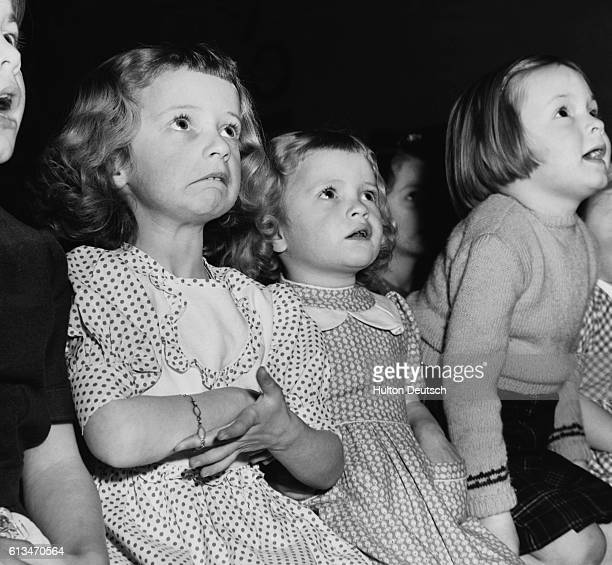 Sisters Francine and Wendy Paine are among an audience of awestruck children at a performance of Dick Wittington put on by employees of the Elmbridge...