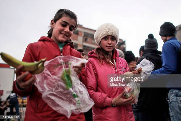 Sisters from Syria carry food distributed by humanitarian aid organisation as migrants wait for their turn at a food distribution stand run by a...