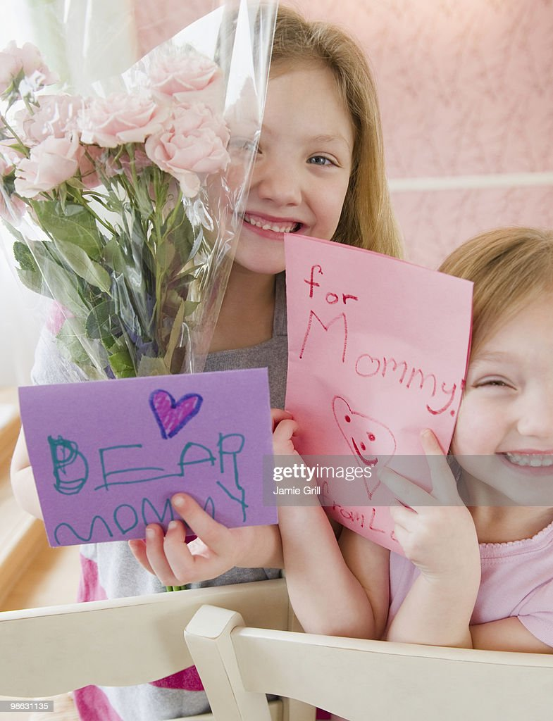 Sisters giving flowers and cards to their mother : Stock Photo