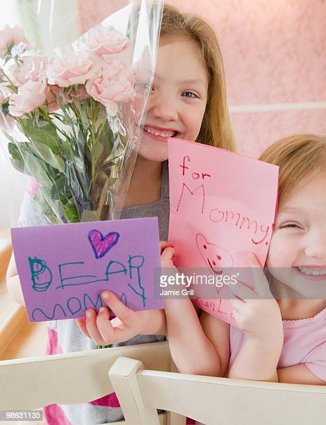 Sisters giving flowers and cards to their mother