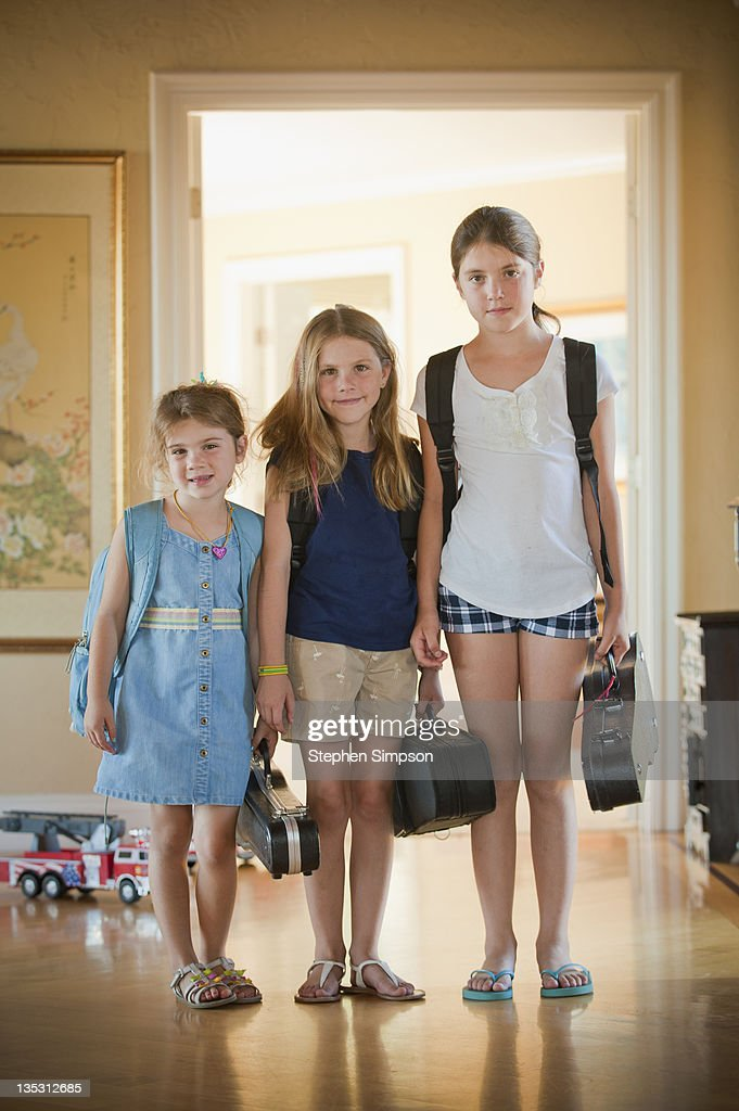 sisters going to school and music classes : Stock Photo