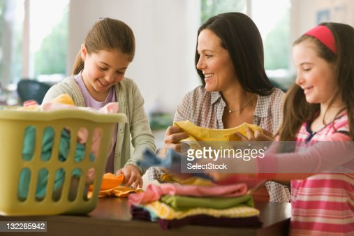 Sisters helping mother with laundry