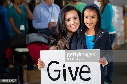 Sisters holding Give sign at winter clothing donation drive