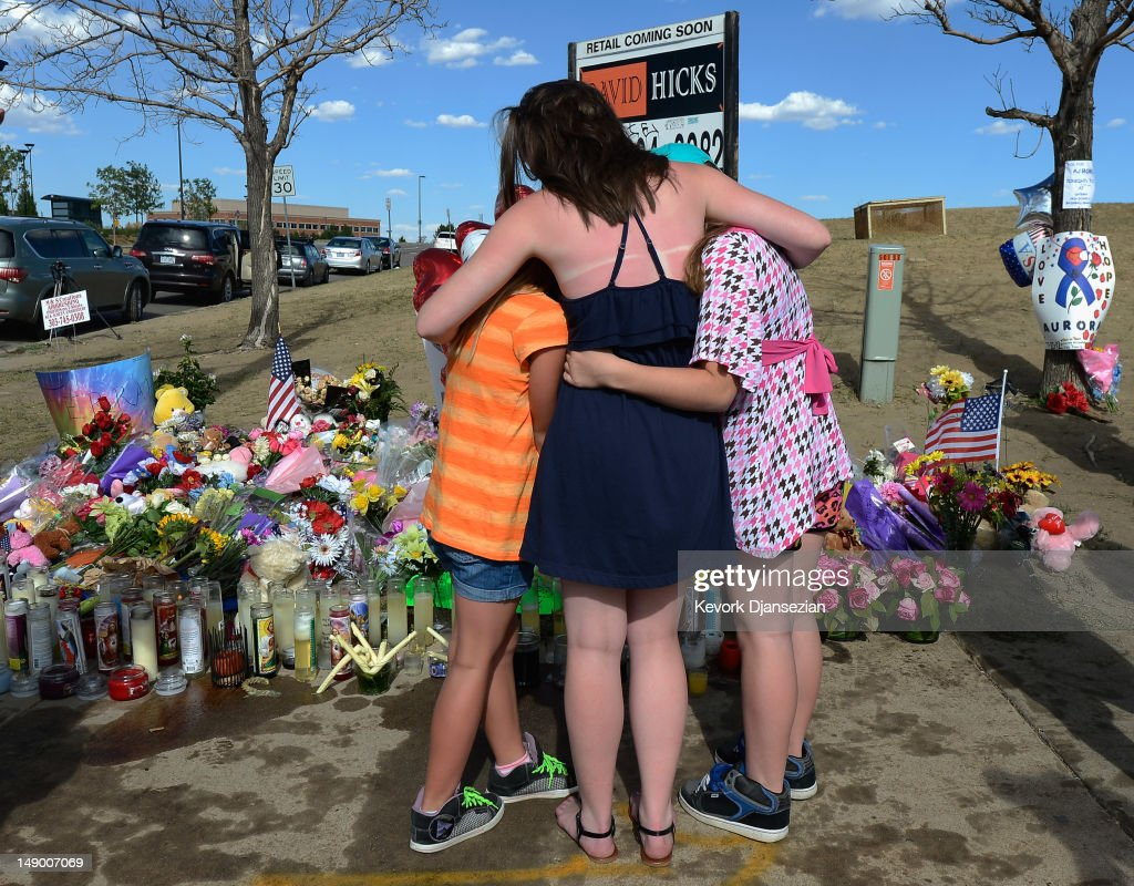 Sisters hug at a makeshift memorial across the street from the Century 16 movie theater the day after a gunman killed 12 people and injured 59 during...