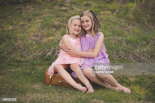 Sisters hugging and smiling in a field.