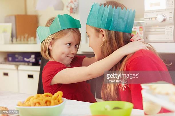 Sisters in paper crowns, hugging