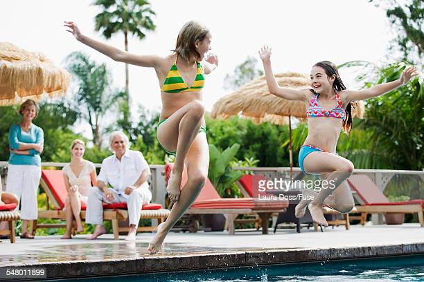 Sisters jumping in to the swimming pool