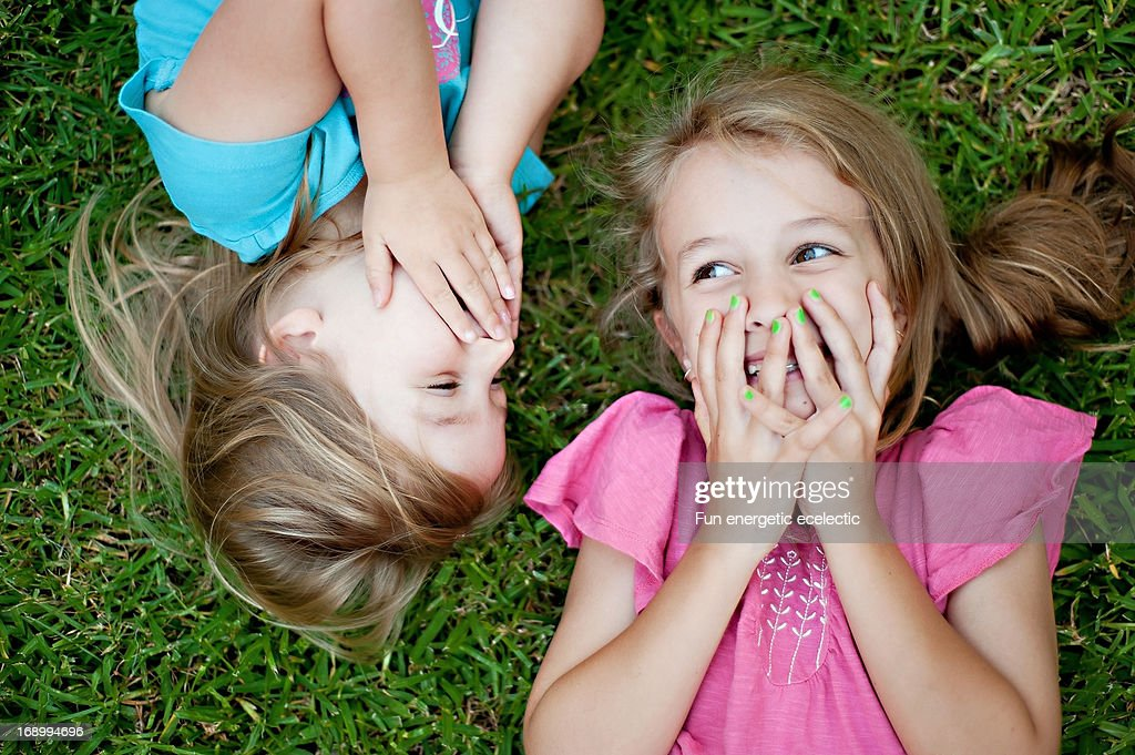 sisters laughing on grass : Stock Photo