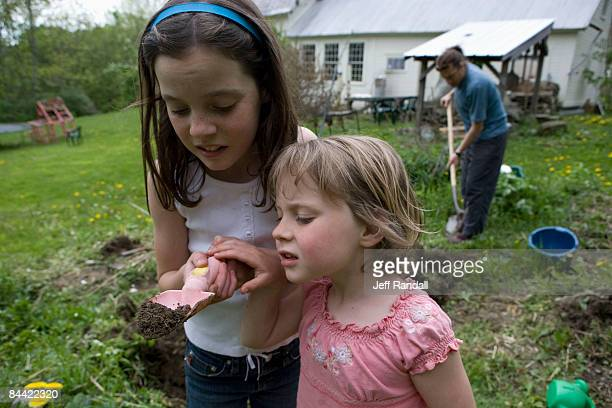 Sisters looking at worms in backyard garden