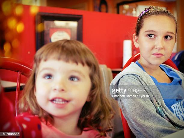 Sisters Looking Away While Sitting In Restaurant