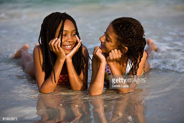 Sisters lying on the water on the beach