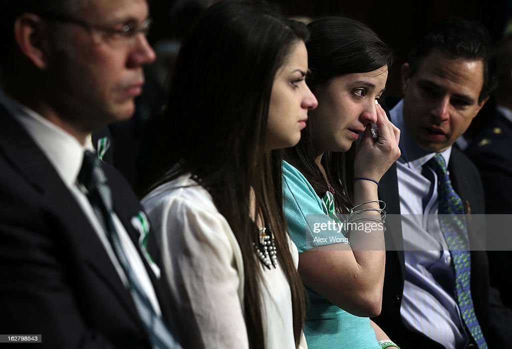 Sisters of Sandy Hook Elementary shooting victim first-grade teacher Victoria Soto, Jillian Soto (3rd L) wipes tears as she listens with Carlee Soto (2nd L) during a hearing before the Senate Judiciary Committee February 27, 2013 on Capitol Hill in Washington, DC. The committee held a hearing on 'The Assault Weapons Ban of 2013.'