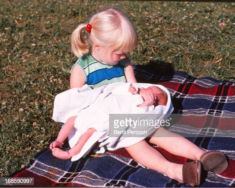 Sisters - older sister holds baby for first time : Stock Photo