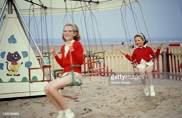 Sisters on swing at beach funfair