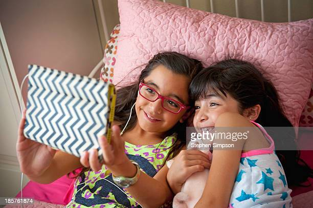 sisters on their bed with tablet computer