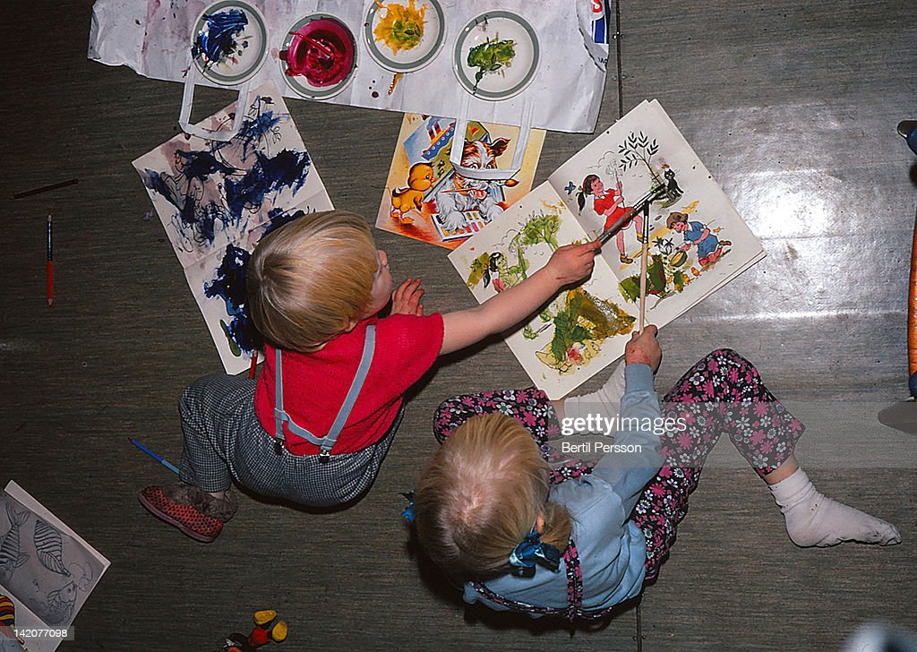 Sisters painting in colouring book in 1960s : Stock Photo