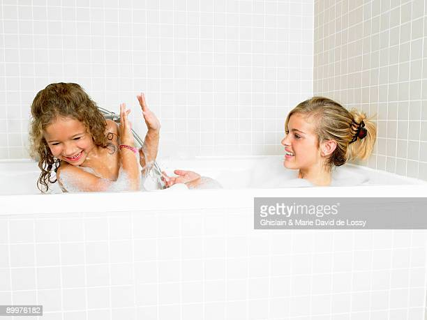 Sisters playing in a bath, foam