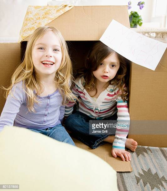 Sisters playing in cardboard box