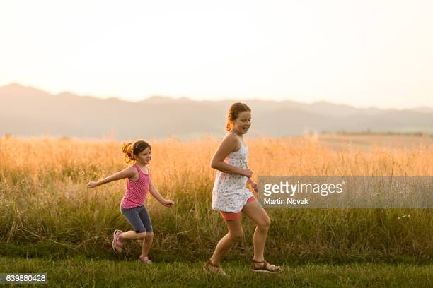Sisters playing in the field on a sunny summer day