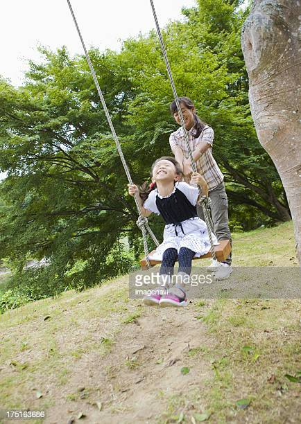 Sisters playing on a swing