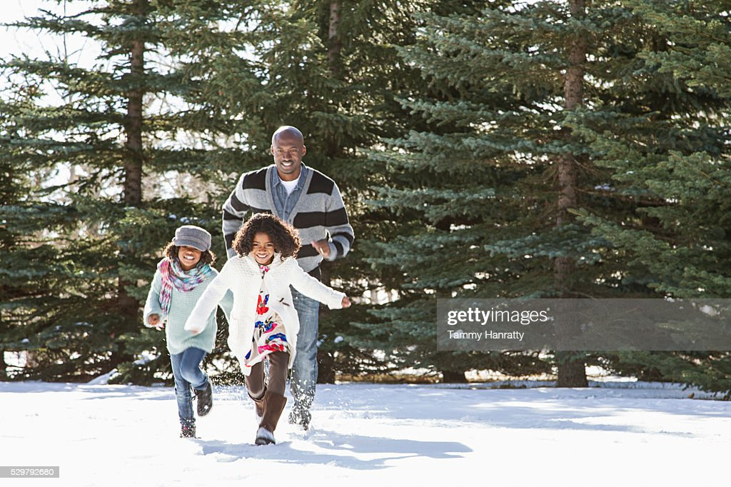 Sisters (8-9,10-12) playing on snow with their father : Stock Photo