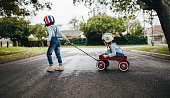 Little girl wearing helmet pulling her sister sitting in a wagon cart on the road. Kids playing outdoors with toy trolley.
