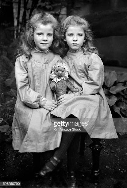 Sisters pose with Steiff teddy bear in England ca 1910