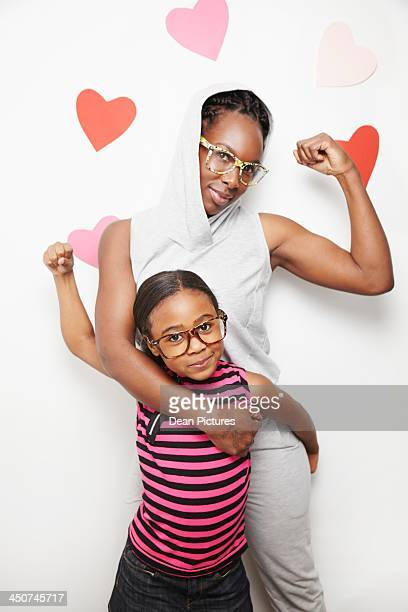 Sisters posing in front of wall with heart print