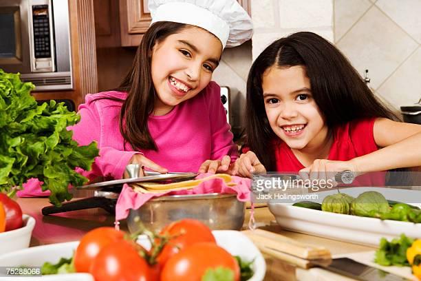 Sisters (8-11) preparing food in kitchen