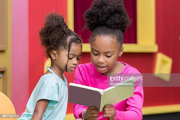 Sisters reading a book together at the library
