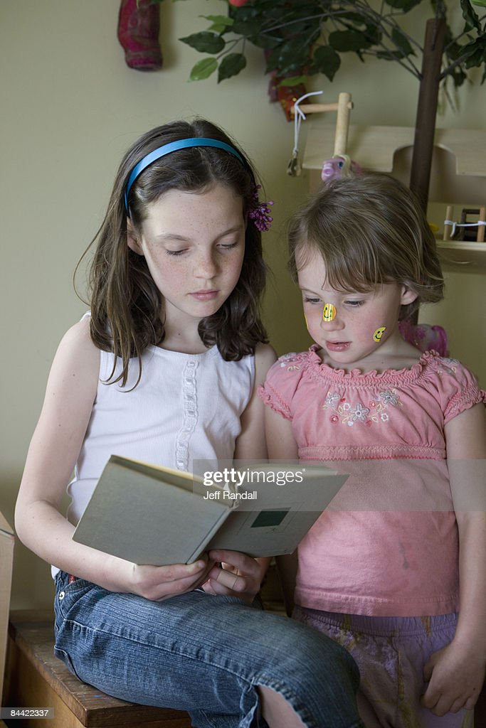 Sisters reading book in playroom : Stock Photo