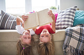 Portrait of two happy blonde sisters having fun at home reading book together lying upside down on sofa and smiling