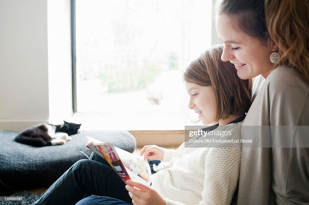 Sisters reading together on sofa : Stock Photo