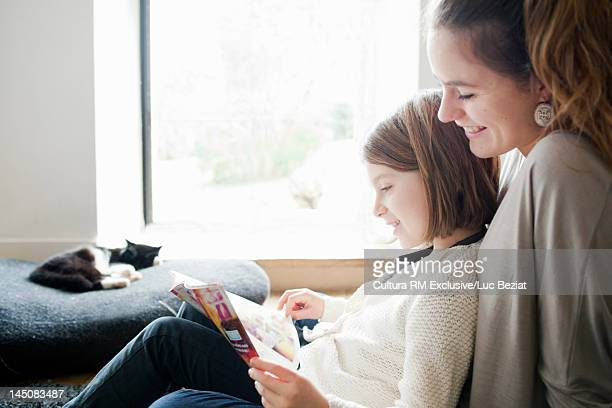 Sisters reading together on sofa